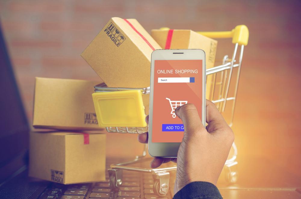 Mann kauft über sein Smartphone im Internet ein.